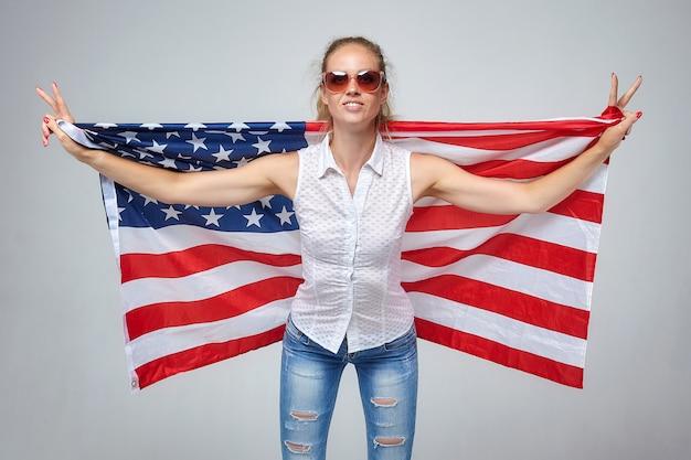 Mulher loira. posando com a bandeira dos eua