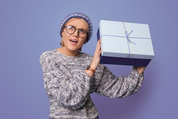 Mulher loira posando de surpresa enquanto agitava um presente na parede azul de um estúdio usando óculos e chapéu