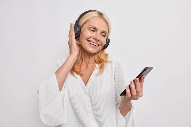 Mulher loira positiva de meia-idade ouve música favorita da lista de reprodução aprecia faixa de áudio popular em fones de ouvido sem fio e usa roupas da moda isoladas sobre a parede branca