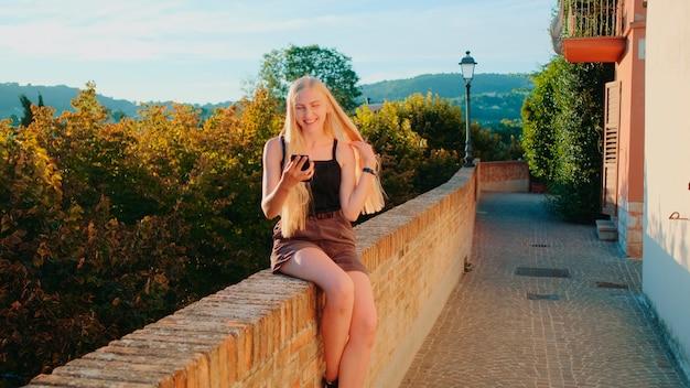 Mulher loira positiva fazendo videochamada com smartphone do local de sua visita