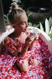 Mulher loira positiva sentada na banheira com flores e segurando a xícara. retrato de mulher bronzeada romântica bebendo chá durante o spa.