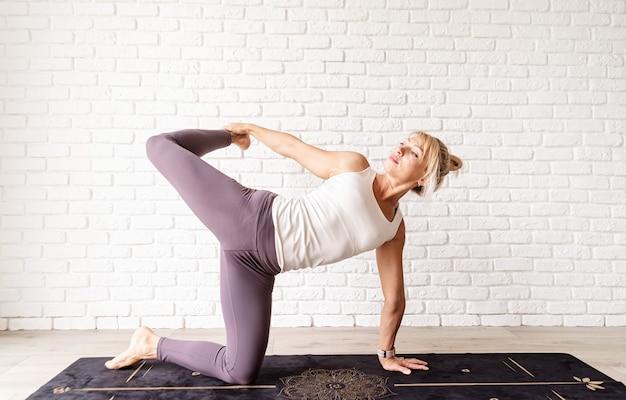 Mulher loira praticando ioga em casa