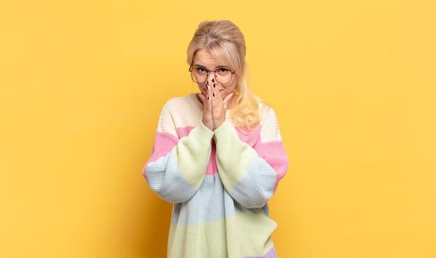 Mulher loira preocupada, esperançosa e religiosa, orando fielmente com as palmas das mãos pressionadas, implorando perdão