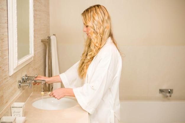Mulher loira prestes a escovar os dentes no banheiro em casa