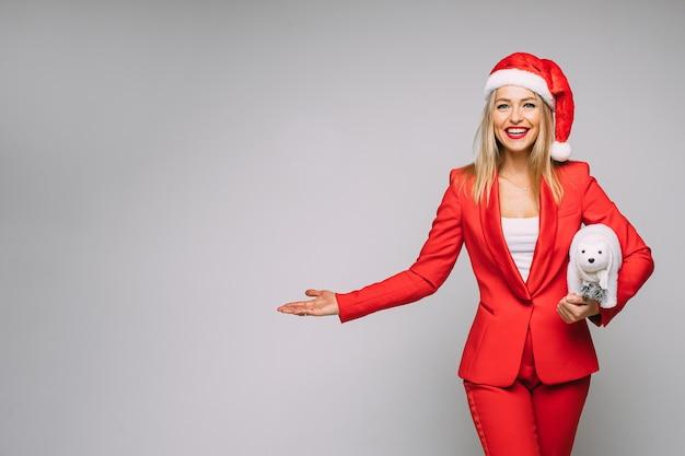 Mulher loira radiante de terno vermelho e chapéu de papai noel segurando um urso polar de brinquedo enquanto gesticula para a direita. copie o espaço