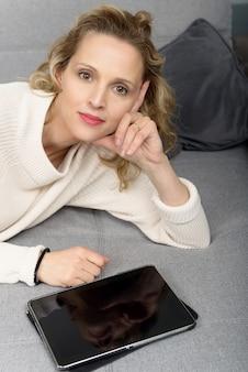 Mulher loira relaxando no sofá com computador tablet