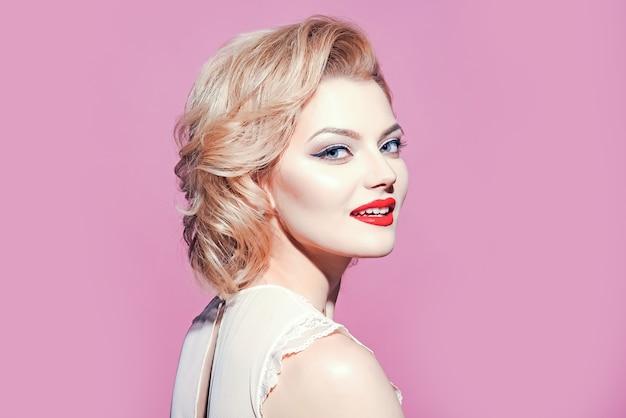 Mulher loira retrô com pincel de maquiagem, vintage, mulher retrô em fundo rosa, copie o espaço.