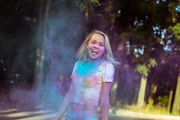 Mulher loira rindo com cabelos esvoaçantes brincando com o pó de holi explodindo ao seu redor