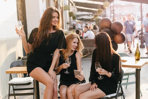 Mulher loira rindo de vestido preto mostrando novo smartphone para amigos enquanto relaxa em um café ao ar livre