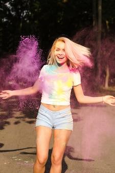 Mulher loira rindo em camiseta branca e shorts jeans brincando com o pó de holi rosa explodindo ao seu redor