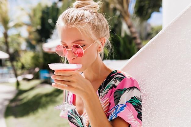 Mulher loira romântica usa óculos de sol, bebendo coquetel com prazer.