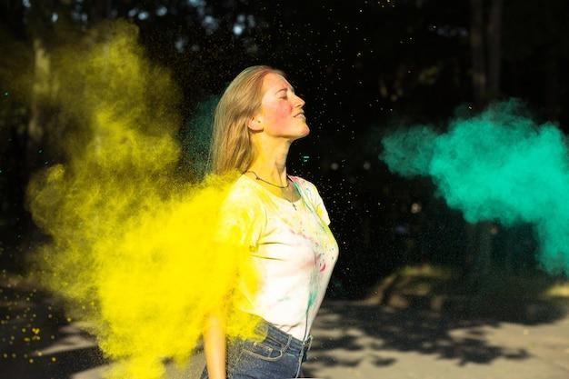 Mulher loira satisfeita brincando com tinta seca amarela e verde holi no parque