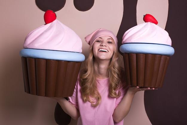 Mulher loira satisfeita com boné rosa e saboreando grandes cupcakes no estúdio
