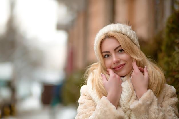 Mulher loira satisfeita com roupas quentes e maquiagem natural posando para a cidade no inverno