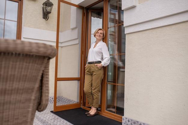 Mulher loira satisfeita em pé na porta da frente aberta