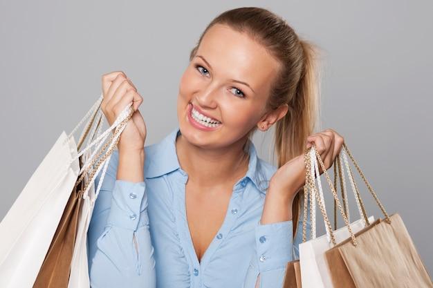 Mulher loira satisfeita segurando sacolas de compras