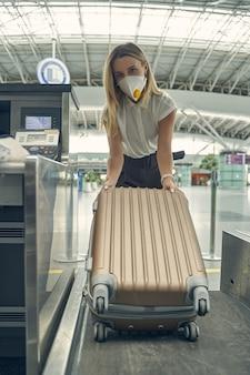 Mulher loira satisfeita usando máscara enquanto se prepara para o voo para a conferência de negócios