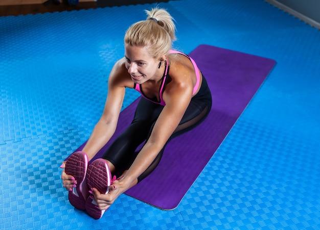 Mulher loira saudável fitness na esteira, fazendo exercícios de aquecimento. uma mulher apta sentada no tapete de ioga e praticando alongamento de pernas e corpo inteiro. estilo de vida saudável, conceito de fitness