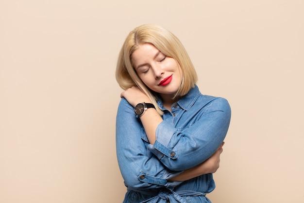 Mulher loira se apaixonando, sorrindo, se abraçando e se abraçando, permanecendo solteira, sendo egoísta e egocêntrica