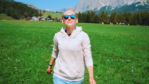 Mulher loira se divertindo correndo no campo natural no verão