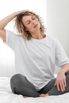 Mulher loira se espreguiçando na cama pela manhã