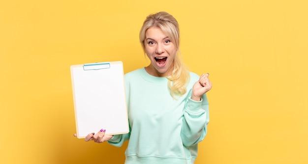 Mulher loira se sentindo chocada, animada e feliz, rindo e comemorando o sucesso, dizendo uau!