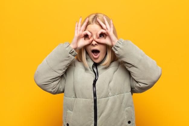 Mulher loira se sentindo chocada, espantada e surpresa, segurando os óculos com olhar surpreso e incrédulo