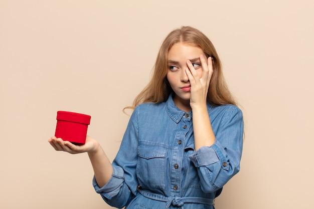 Mulher loira se sentindo entediada, frustrada e com sono após uma tarefa cansativa, enfadonha e tediosa, segurando o rosto com a mão