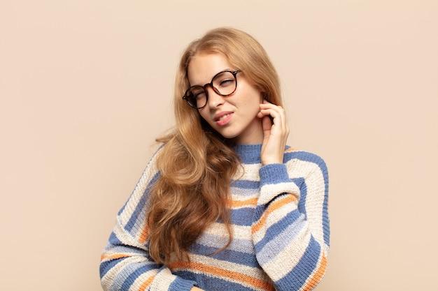 Mulher loira se sentindo estressada, frustrada e cansada, esfregando o pescoço dolorido, com uma aparência preocupada e preocupada