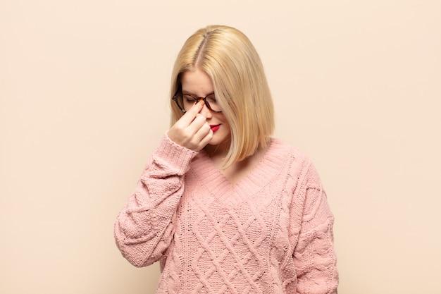 Mulher loira se sentindo estressada, infeliz e frustrada, tocando a testa e sofrendo de enxaqueca ou forte dor de cabeça