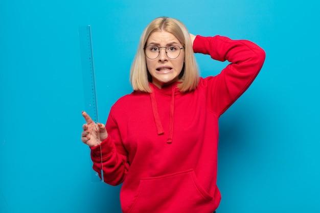 Mulher loira se sentindo estressada, preocupada, ansiosa ou com medo, com as mãos na cabeça, entrando em pânico com o erro