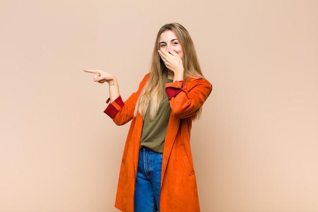 Mulher loira se sentindo feliz, chocada e surpresa, cobrindo a boca com a mão e apontando para o espaço lateral da cópia