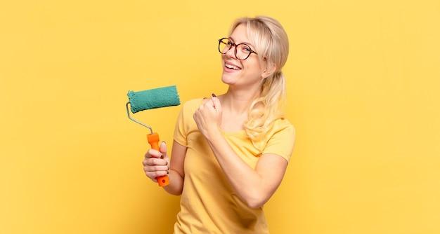 Mulher loira se sentindo feliz, positiva e bem-sucedida, motivada para enfrentar um desafio ou comemorar bons resultados