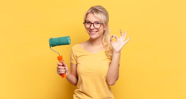 Mulher loira se sentindo feliz, relaxada e satisfeita, mostrando aprovação com gesto de ok, sorrindo