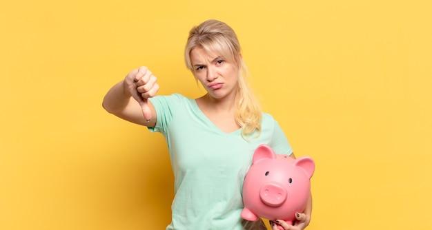 Mulher loira se sentindo mal, irritada, irritada, decepcionada ou descontente, mostrando o polegar para baixo com um olhar sério