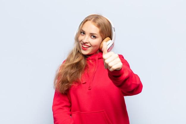 Mulher loira se sentindo orgulhosa, despreocupada, confiante e feliz, sorrindo positivamente com o polegar para cima