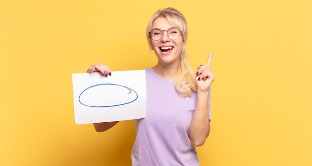Mulher loira se sentindo um gênio feliz e empolgado depois de realizar uma ideia, levantando alegremente o dedo, eureka!