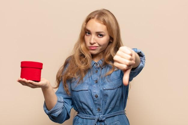 Mulher loira se sentindo zangada, irritada, decepcionada ou descontente, mostrando o polegar para baixo com um olhar sério