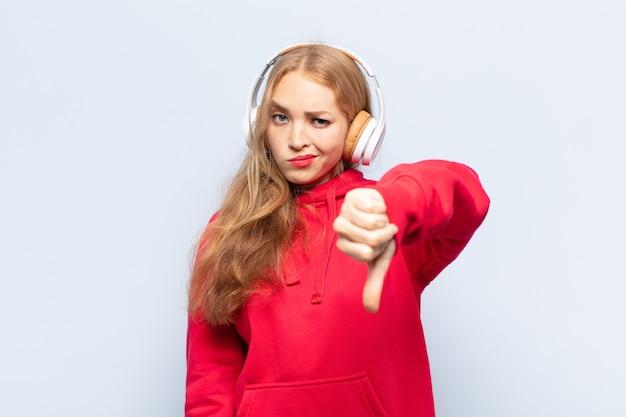 Mulher loira se sentindo zangada, irritada, desapontada ou descontente, mostrando o polegar para baixo com um olhar sério