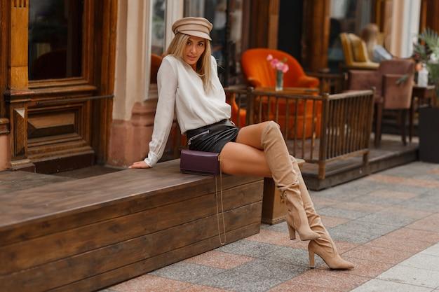 Mulher loira sedutora com pernas perfeitas sentada no banco