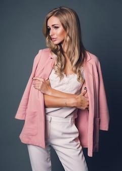 Mulher loira sedutora em jaqueta rosa posando