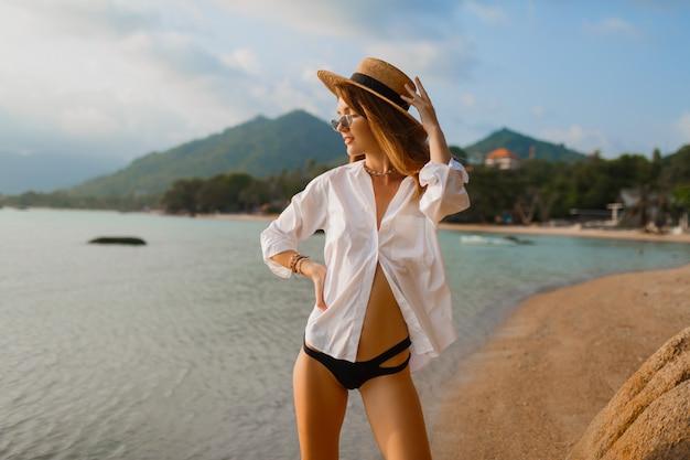 Mulher loira sedutora na blusa branca posando na praia tropical
