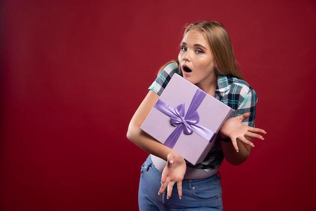 Mulher loira segura com força uma caixa de presente e fica com ciúmes de compartilhar.