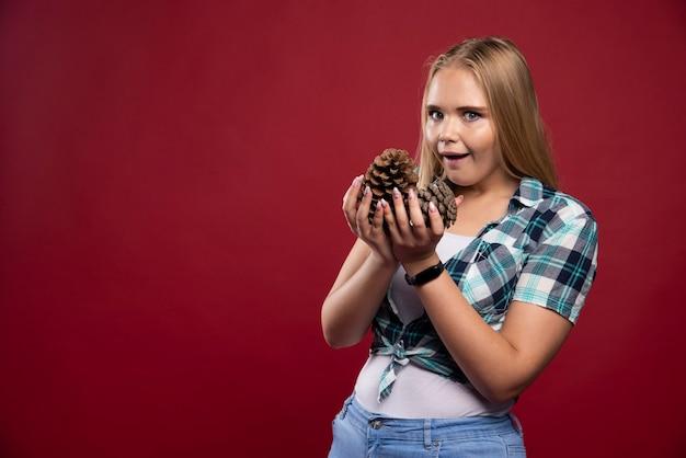 Mulher loira segura o cone do carvalho na mão e faz poses surpresas.