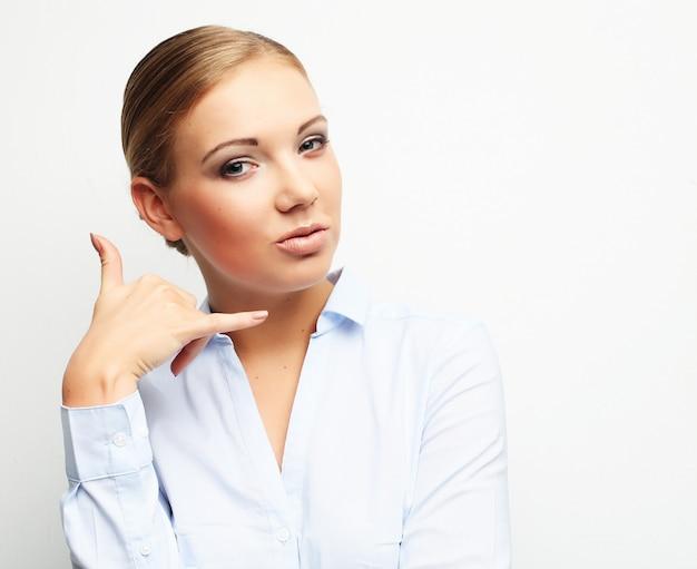 Mulher loira segurando a mão perto da orelha como um telefone