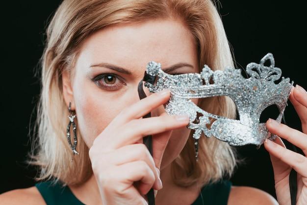 Mulher loira segurando a máscara de prata na mão