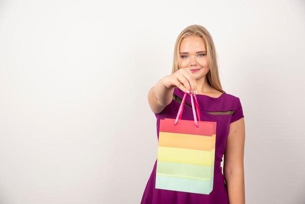 Mulher loira segurando a sacola de presente com uma expressão feliz.