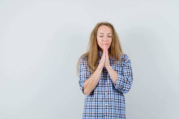 Mulher loira segurando as mãos em gesto de oração na camisa e parecendo esperançosa,