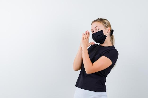 Mulher loira segurando as mãos em posição de oração em uma camiseta preta