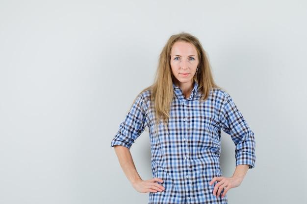 Mulher loira segurando as mãos na cintura com uma camisa e parecendo tentadora,